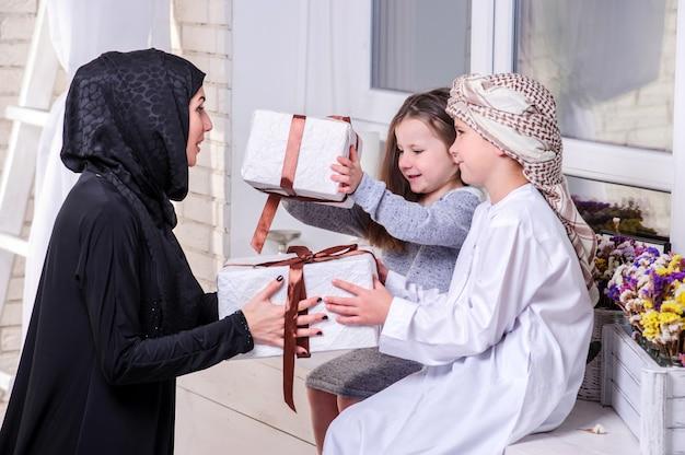 アラビア語の母と子供たちがギフトでポーズします。