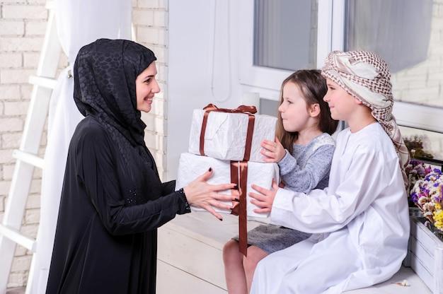 아랍어 어머니와 아이 선물로 포즈입니다.