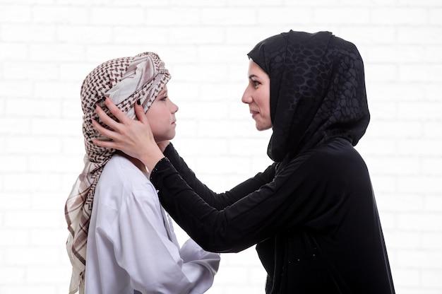 아랍어 어머니와 아들이 실내에서 포즈를 취하고 있습니다.