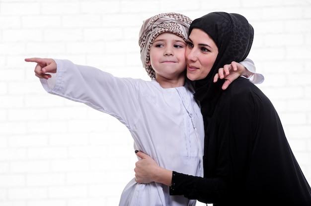 アラビア語の母と息子が室内でポーズします。