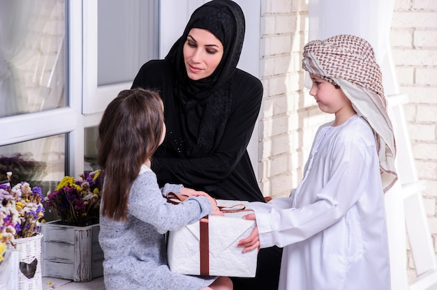 Arabic mother giving gift to her kids.