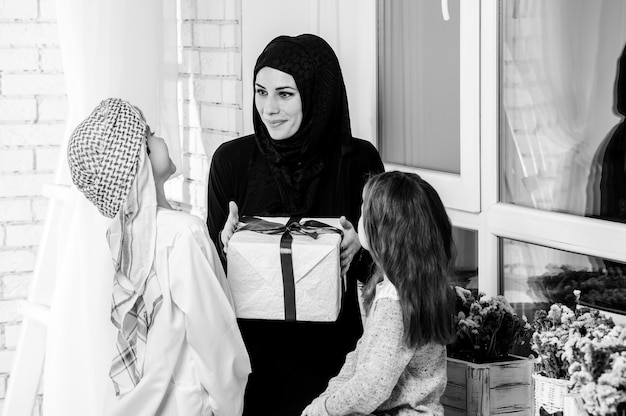 Arabic mother and kids posing with gift.indoors.