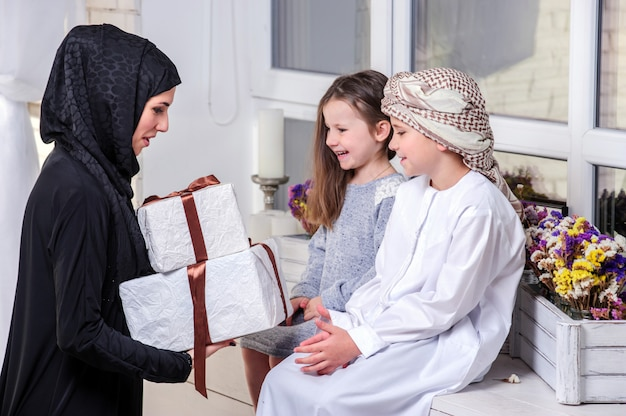Arabic mother and kids posing with gift.