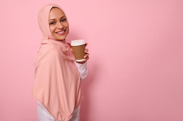 히잡으로 머리를 덮은 아랍 이슬람 아름다운 여성은 뜨거운 음료의 일회용 판지에서 테이크아웃 컵을 들고 분홍색 배경에 4분의 3을 서서 카메라를 바라보며 미소를 짓습니다. 복사 공간