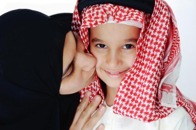 彼女の幼い息子にキスするアラビアのイスラム教徒の母親