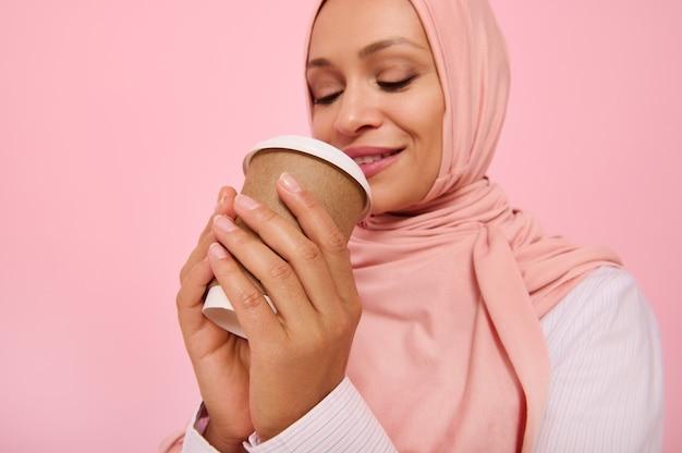 히잡으로 머리를 덮고 일회용 판지 테이크아웃 컵에서 뜨거운 음료, 차 또는 커피를 마시는 아랍 무슬림 예쁜 여성, 색색의 배경에 4분의 3 서서 복사 공간. 확대