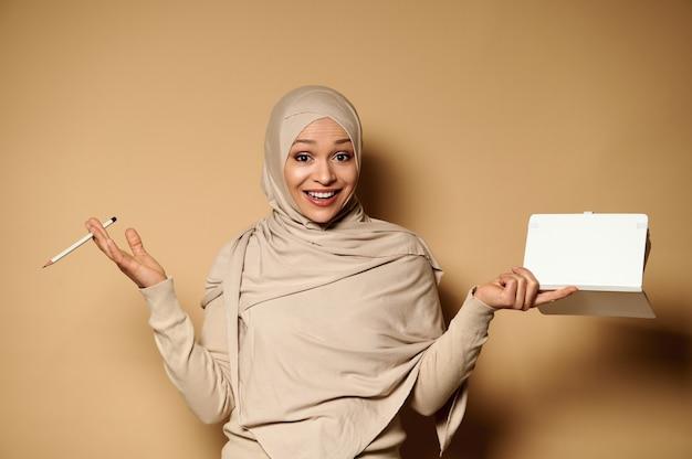 日記を持って、美しい歯を見せる笑顔でカメラを見て、コピースペースのあるベージュに白い鉛筆で指しているヒジャーブのアラビアのイスラム教徒の女性。