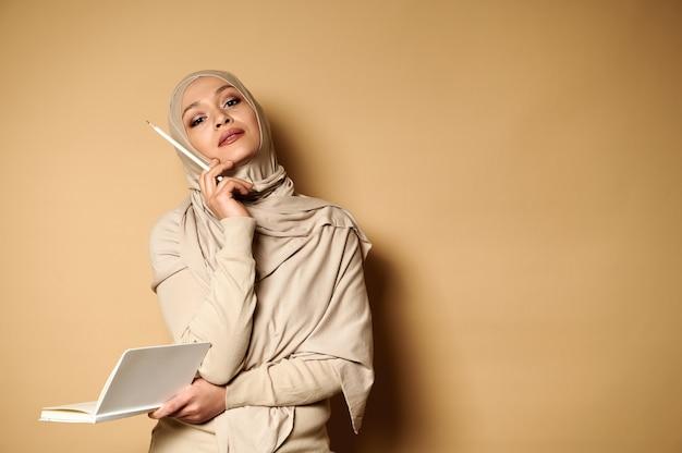 ベージュのヒジャーブを身に着けているアラビアのイスラム教徒の女性は、日記を持って、コピースペースのあるベージュの上に白い鉛筆で指差しながら、思慮深く見上げます。