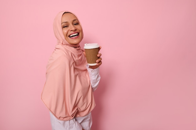 분홍색 히잡으로 머리를 덮은 아랍 이슬람 여성은 일회용 판지 테이크아웃 컵을 들고 이빨 미소를 짓고 카메라를 보며 복사 공간이 있는 유색 배경에 3/4 서 있습니다