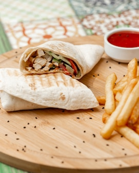 Arabic shaurma in lavash with french fries and tomato sauce.