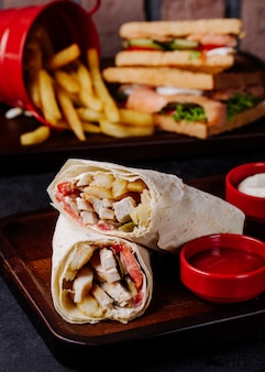 Arabic shaurma in lavash with fries and club sandwiches behind.