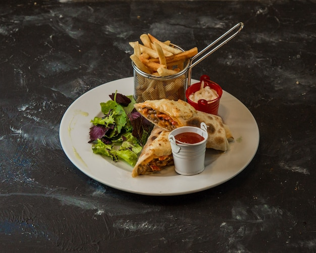 Arabic shaurma serbed with fries, sauce and green salad.