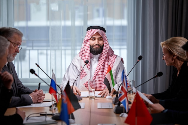 Arabic sheikh executive listening attentively to one of speakers delegates report, listening for ideas for success investments at bright modern office room. people in formal wear at press conference.