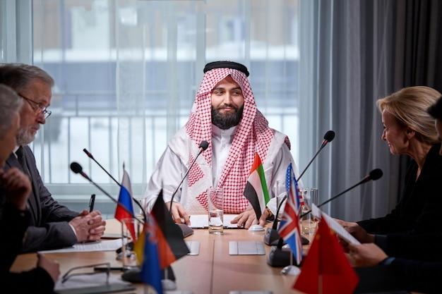 スピーカーの代表者の報告の1つに注意深く耳を傾け、明るくモダンなオフィスルームで成功する投資のアイデアを聞いているアラビア語のシェイクエグゼクティブ。記者会見で正装の人。