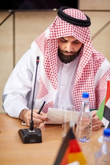 Arabic sheikh man wearing traditional emirates clothes sits at desk on business meeting, male saudi arab arabic business muslim looking at document