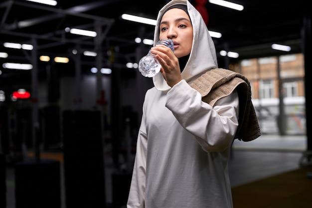 ボトルを保持しているジムの飲料水で白いヒジャーブに身を包んだアラビアのスポーツフィットネス女性は、トレーニング、スポーツ運動の後に休息を取ります。肖像画