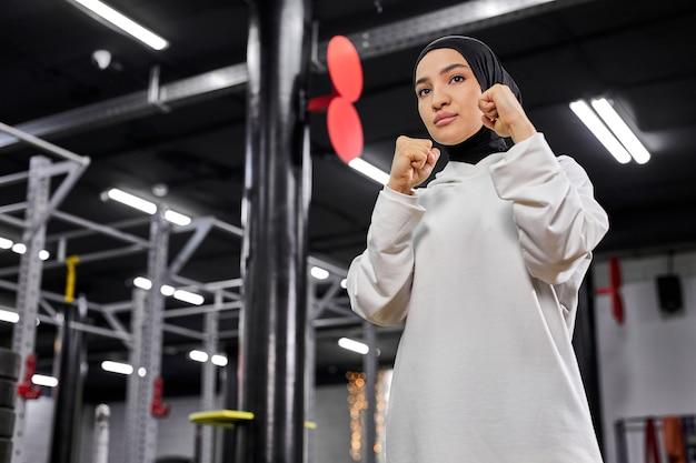 戦闘機のポーズで立っているアラビアのスポーツウーマン、打つつもり、フィットネスセンターでボクシングに従事、白いヒジャーブを身に着けています。スポーツ、トレーニング、フィットネスのコンセプト