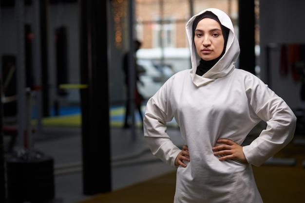 아랍어 sportswoman는 훈련 후 체육관에서 포즈, 흰색 hijab 포즈에서 이슬람 여자의 초상화, 카메라를 찾고 서 있습니다.
