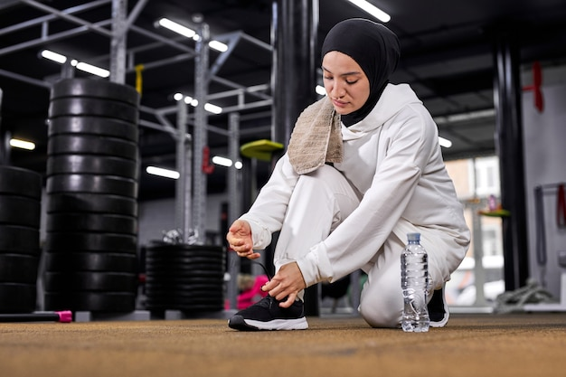 アラビアのスポーツウーマンがスニーカーにひもを結び、ジムでのトレーニングの準備をしている、白いスポーツヒジャーブを着用