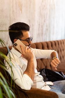 수염을 기른 흰 셔츠를 입은 아랍의 성공한 사업가나 노동자가 전화기 근처에 전화를 걸고 있다