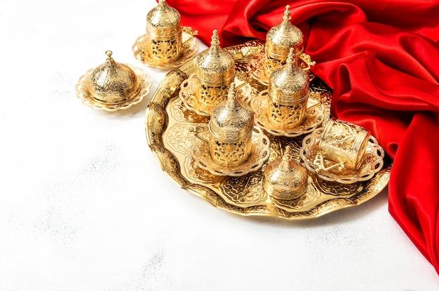 Арабский чайный кофейный сервиз с золотыми чашками и красным декором. концепция гостеприимства