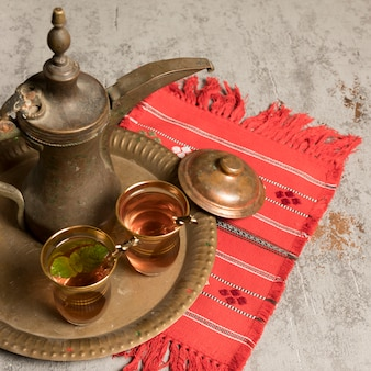 Arabic tea in glasses with teapot on cloth