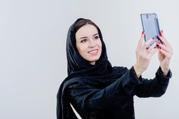 Arabic way dressed woman taking selfie using mobile camera.