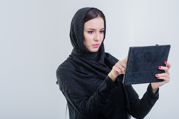 Arabic way dressed woman working using tablet.