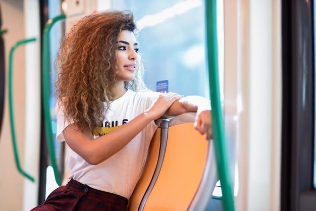 地下鉄の列車の中のアラビアの女性。カジュアルな服装のアラブの女の子