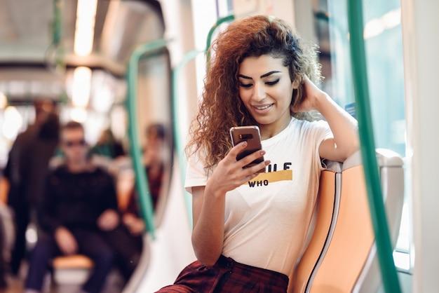 彼女のスマートフォンを見て地下鉄の列車の中のアラビアの女性