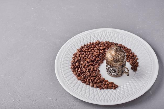 하얀 접시에 arabica 콩입니다.