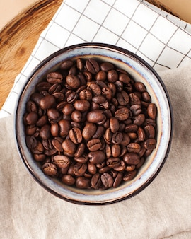 Arabica coffee beans in a ceramic bowl on a wooden tray on a brown background for coffee houses and ...