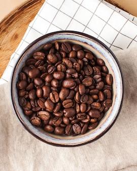 コーヒーハウスと...のための茶色の背景の木製トレイ上のセラミックボウルのアラビカコーヒー豆。