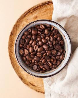 Кофейные зерна арабики в керамическом шаре на деревянном подносе на коричневой предпосылке. вертикальное фото для кофеен и кафе.