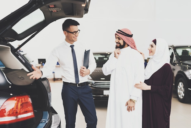 Arabs buy car examining car trunk with dealer.