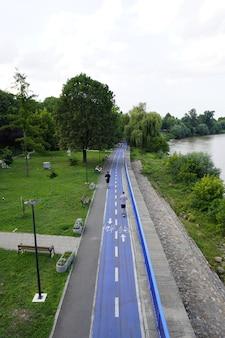 Арад, румыния, 20 июля 2021 года, велосипедная дорожка, велосипедная дорожка в парке, люди на электросамокатах, река