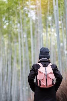 Молодая женщина путешествуя на бамбуковой роще arashiyama, счастливый азиатский путешественник смотря лес бамбука sagano. достопримечательности и популярные для туристов достопримечательности в киото, япония. концепция путешествия по азии