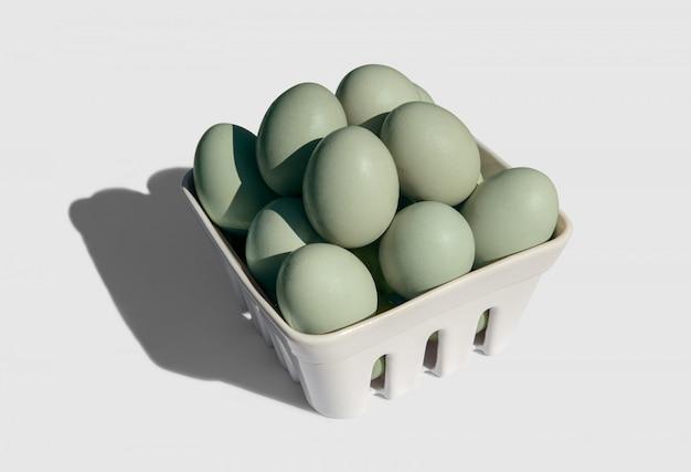 Араукана яйца на корзине, изолированные на белом. синие или зеленые яйца из курицы араукана