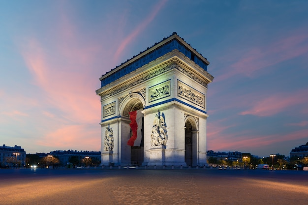 Arc de triomphe paris and champs elysees with a large france flag at paris, france.