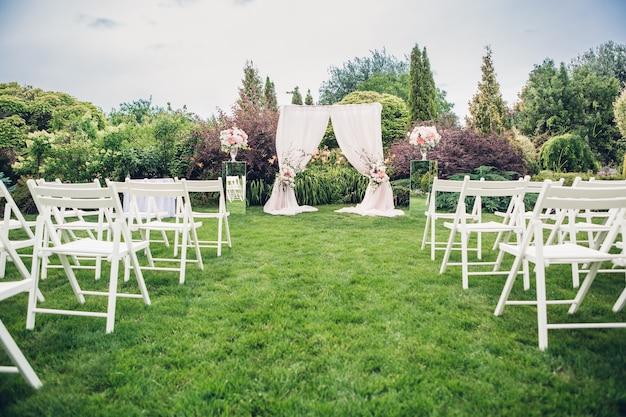 Арка и стулья для свадебной церемонии, декорированные тканью и цветочными композициями.