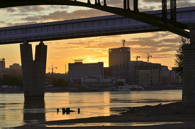 ノボシビルスクの背の高い家々に昇る太陽がオビ川を渡るアーチとメトロの橋