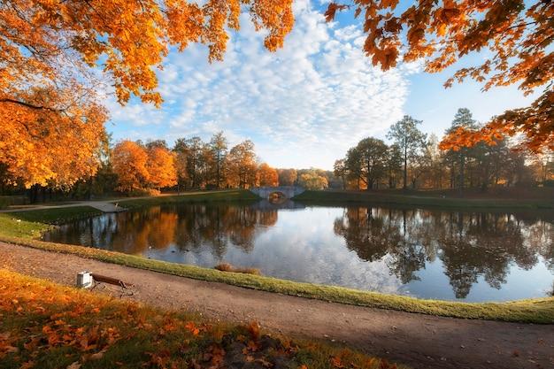 Arch bridge in a beautiful gatchina park in leningrad region  in golden autumn sunny day