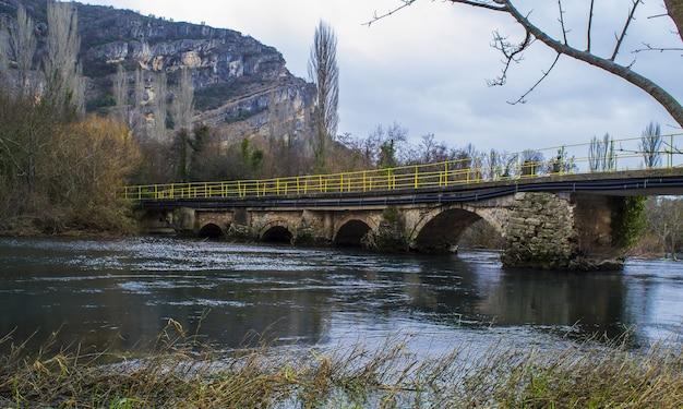 クロアチアのクルカ国立公園の岩に囲まれた川に架かるアーチ橋