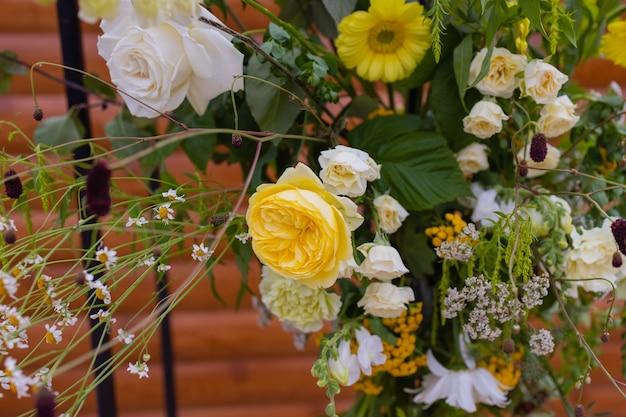 Арка для свадебной церемонии, украшенная тканью цветами и зеленью, находится в сосновом лесу.