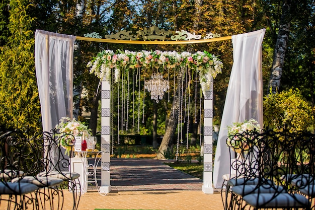 結婚式のアーチ。クリスタルのシャンデリアと生花で飾られました。結婚式の装飾。新婚夫婦。