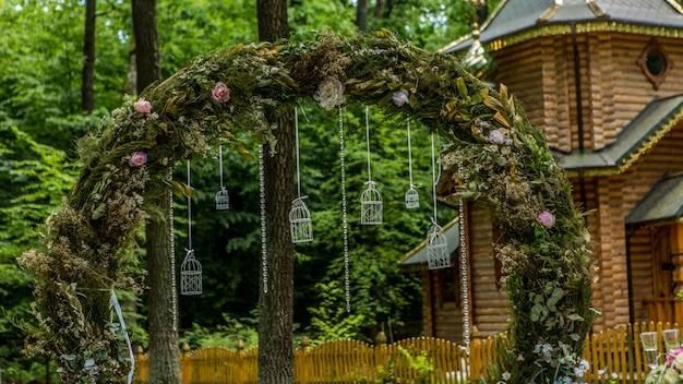 결혼식을위한 아치. 패브릭 꽃과 녹지로 장식되어 있습니다. 소나무 숲에 위치하고 있습니다. 배경 교회. 소박한 스타일의 웨딩 장식. 그냥 결혼 했어요 웨딩 장식.