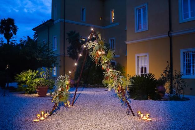 Арка для свадебной церемонии в вечернее время в виде треугольной избы, украшенной цветами и лампочками.