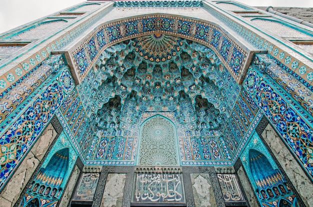 Arch of the mosque in blue tones is made from the mosaic of the islamic religion.