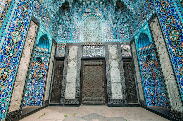 The arch of the mosque in blue tones is made from the mosaic of the islamic religion.