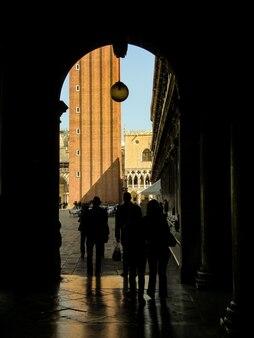 그림자와 그림자 통과 관광객과 베니스의 세인트 마크 광장 뒤에 깊은 그림자에 아치 또는 문.